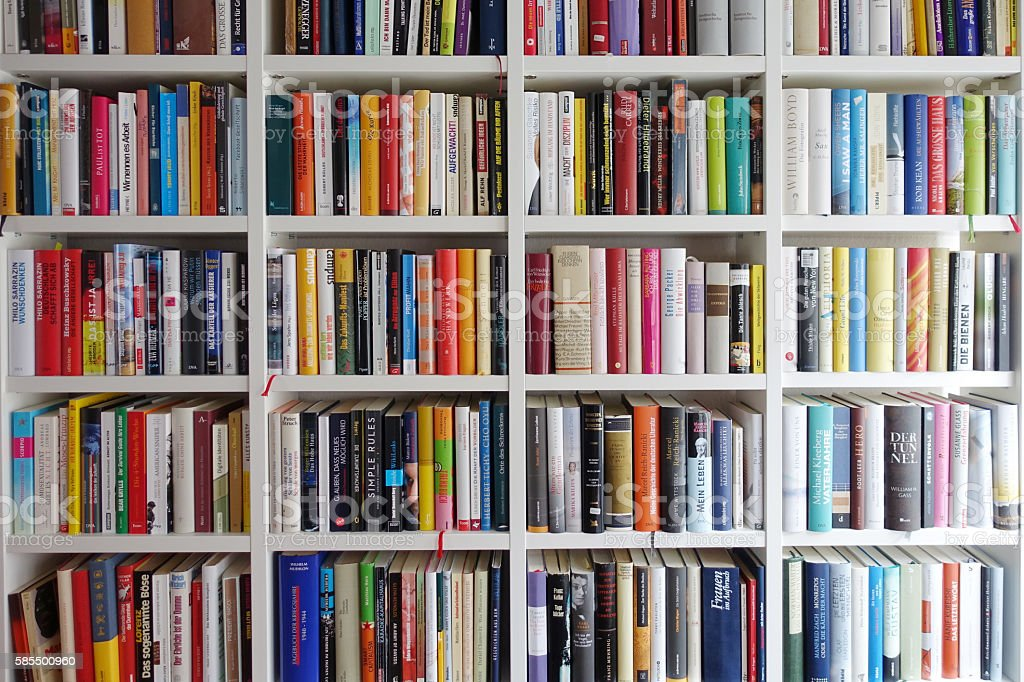 White book shelves narrowly packed with german books stock photo