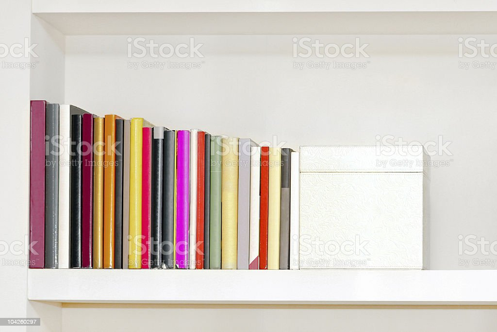 White bookshelf with colorful lineup of books  royalty-free stock photo