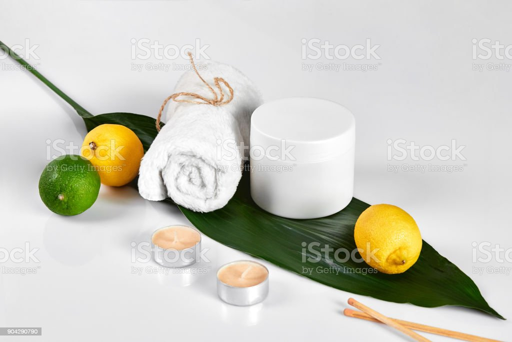 White bottle and two whole lemon and lime isolated on white background. The concept for advertising cosmetics stock photo