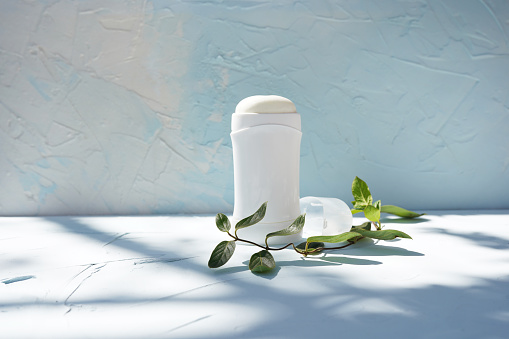 White bottle of dry deodorantat and green branch at blue concrete wall