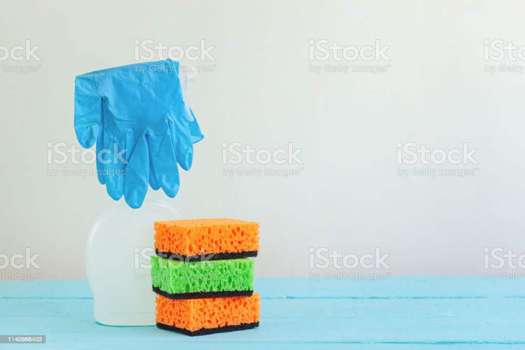 White bottle spray cleaner and clean sponge on a table. Cleaning...
