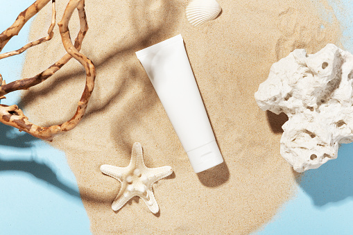 White bottle with skincare product. Summer decorations on sand. Starfish and seashell around cosmetology tube. Mockup style. Wellness and beauty concept