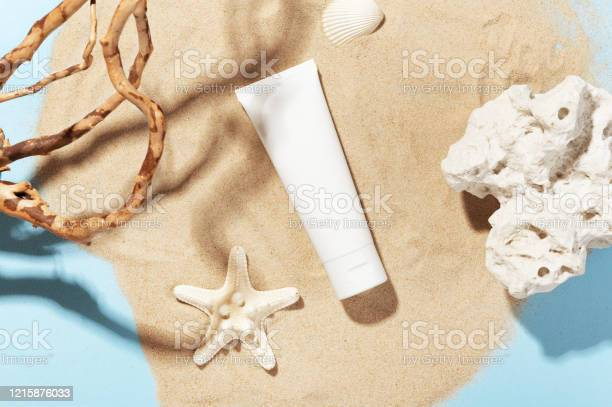Photo of White bottle with skincare product. Summer decorations on sand. Starfish and seashell around cosmetology tube. Mockup style. Wellness and beauty concept
