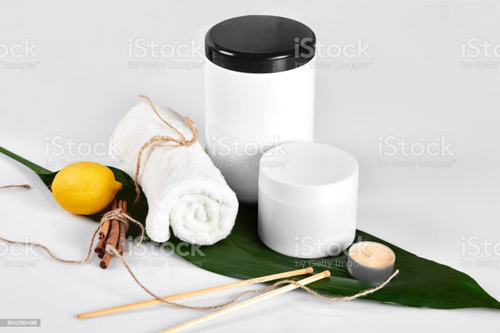 White bottles and one whole lemon isolated on white background. The concept for advertising cosmetics stock photo