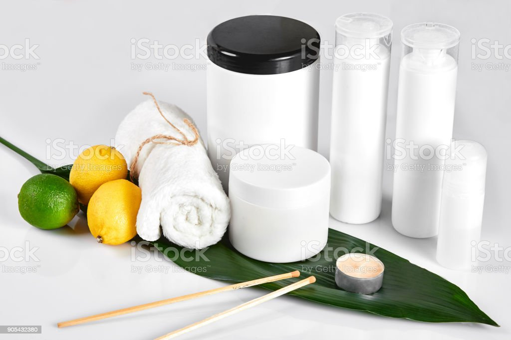 White bottles and two whole lemon and lime isolated on white background. The concept for advertising cosmetics stock photo