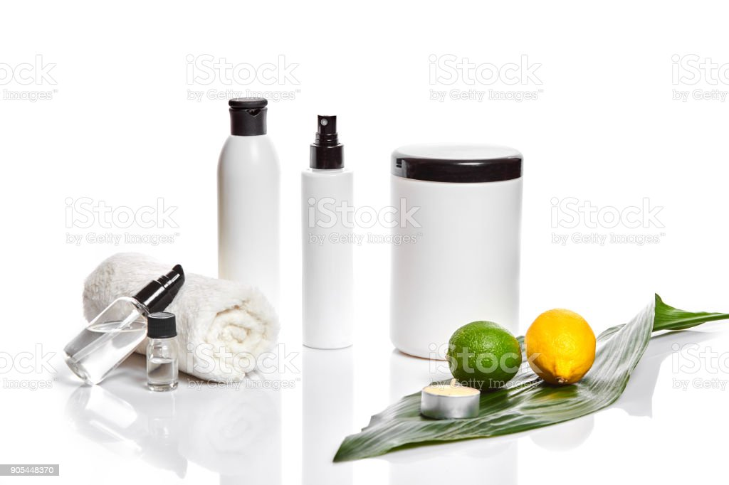 White bottles and whole lemon and lime isolated on white background. The concept for advertising cosmetics stock photo