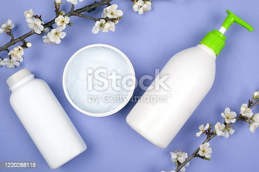 847096968 istock photo white bottles with cosmetics flowering spring apricot branches copy space on purple background.  beauty 1220288115