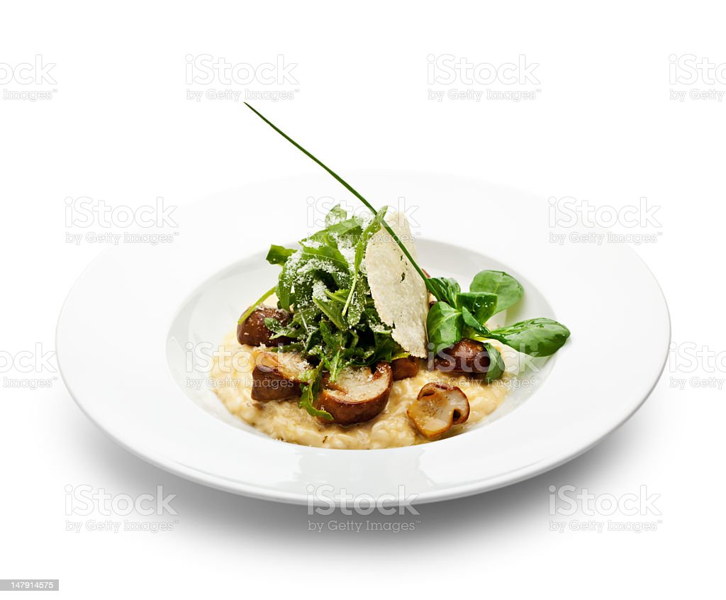 White bowl containing mushroom risotto and basil stock photo