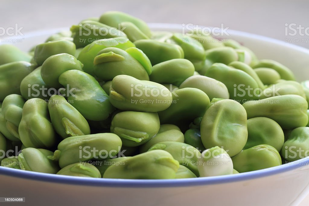 A white bowl filled with green broad beans stock photo