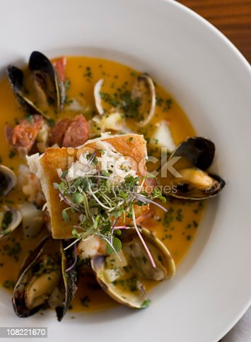 Hearty seafood soup with mussels, clams and a grilled filet of sea bass in a saffron curry broth.  Sea bass is topped with cooked crabmeat and the whole dish is sprinkled with chopped parsley.
