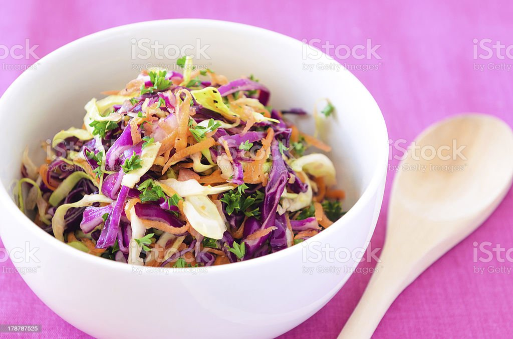 A white bowl full of fresh coleslaw with wood spoon on pink stock photo