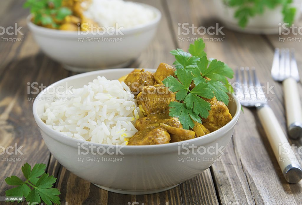 White bowl of chicken curry with rice on wooden table stock photo