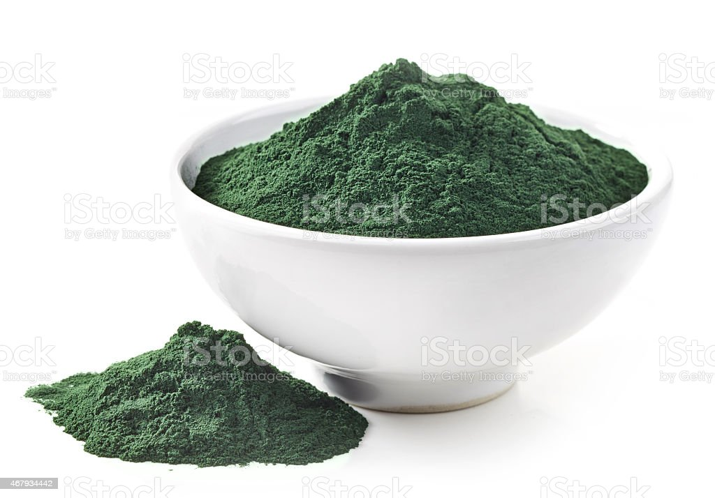 White bowl of green spirulina algae powder spilling out stock photo