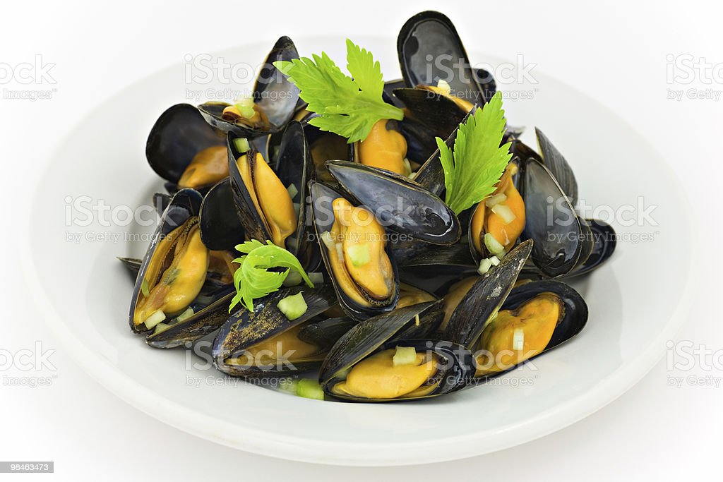 A white bowl of mussels with green garnishes royalty-free stock photo