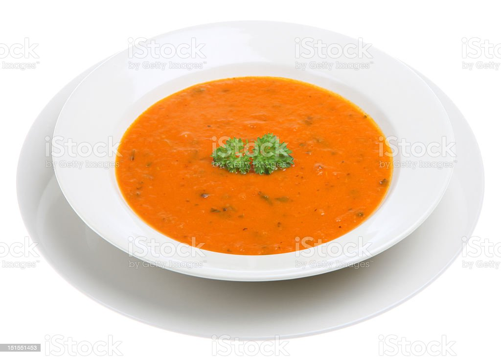 White bowl of tomato soup with sprig of basil on top stock photo