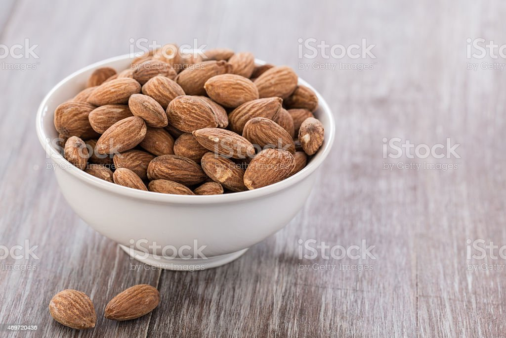 White Bowl With Almonds on Wood Background stock photo
