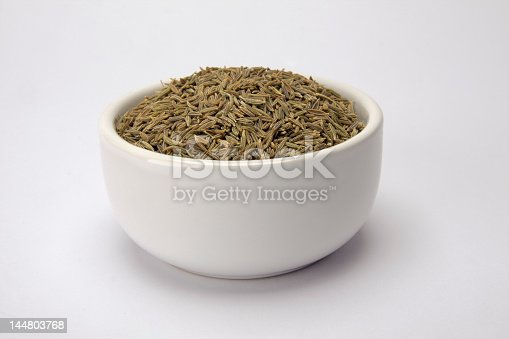 Cumin seeds in a small white bowl isolated on a white background