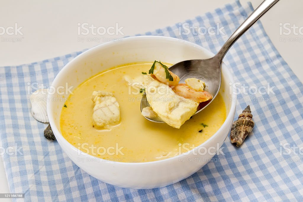 White bowl with fish soup on a blue and white tablecloth stock photo