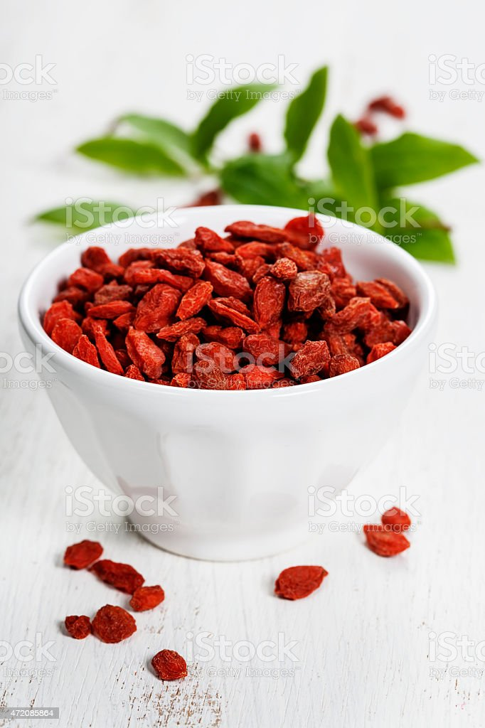 white bowl with goji berries on the table stock photo