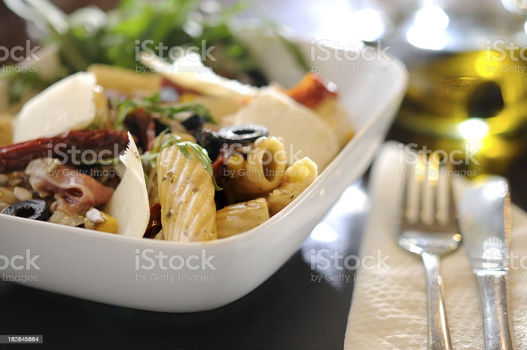 White bowl with pasta dinner, salad and fork stock photo