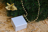 White box with a gift, Christmas wreath, Christmas tree decorations. Close-up.
