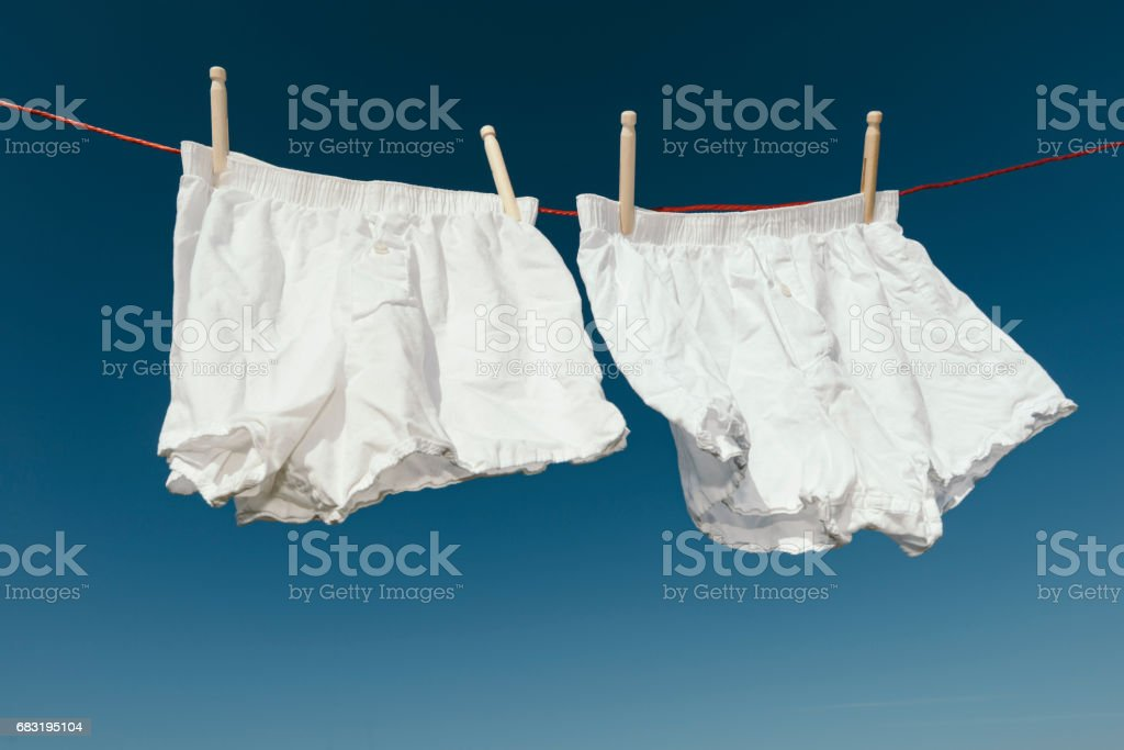 white Boxer shorts on a clothes line against blue sky. stock photo