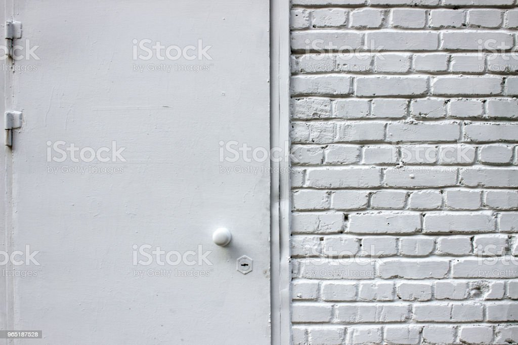 White brick wall. Metal door with round handle and borehole royalty-free stock photo