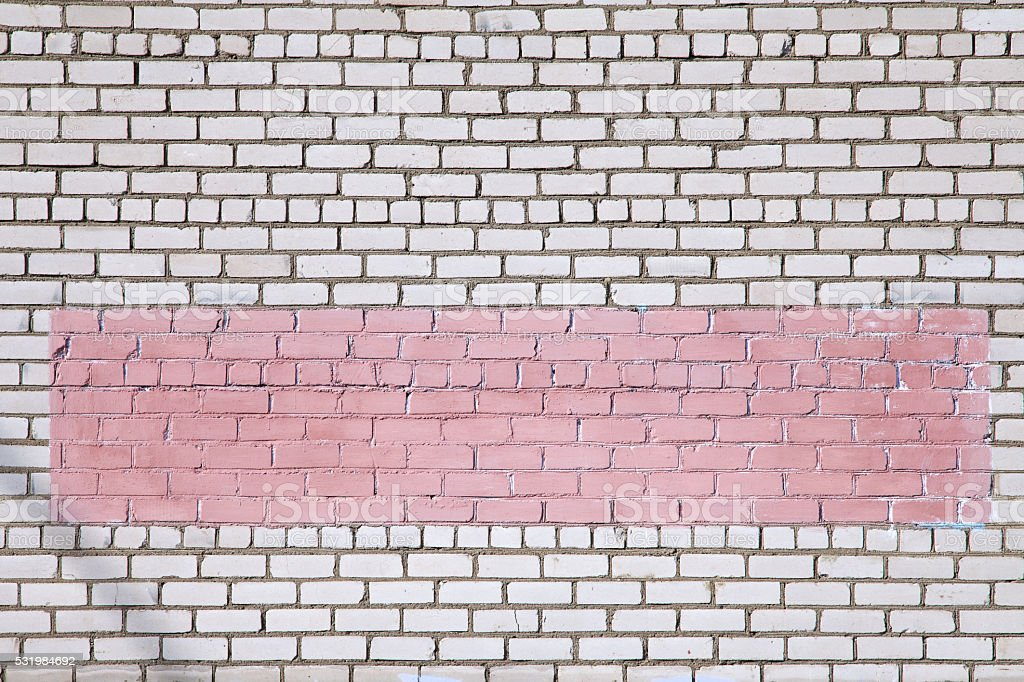 White brick wall with graffiti painted over with pink paint stock photo