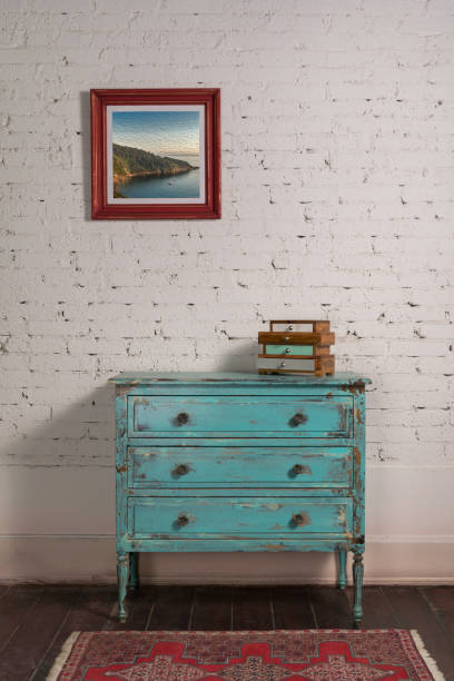 White brick wall with shabby chic vintage turquoise cabinet and hanged painting stock photo