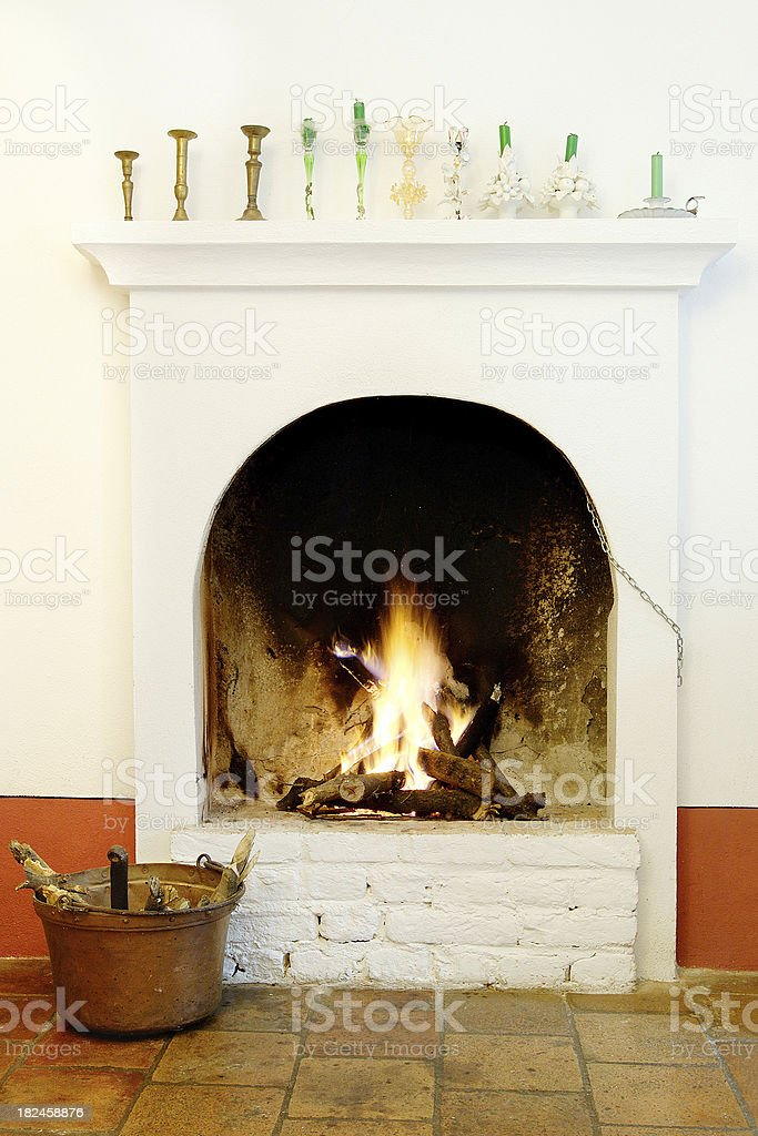 White bricks fireplace with fire burning, candle holders, terracotta floor royalty-free stock photo
