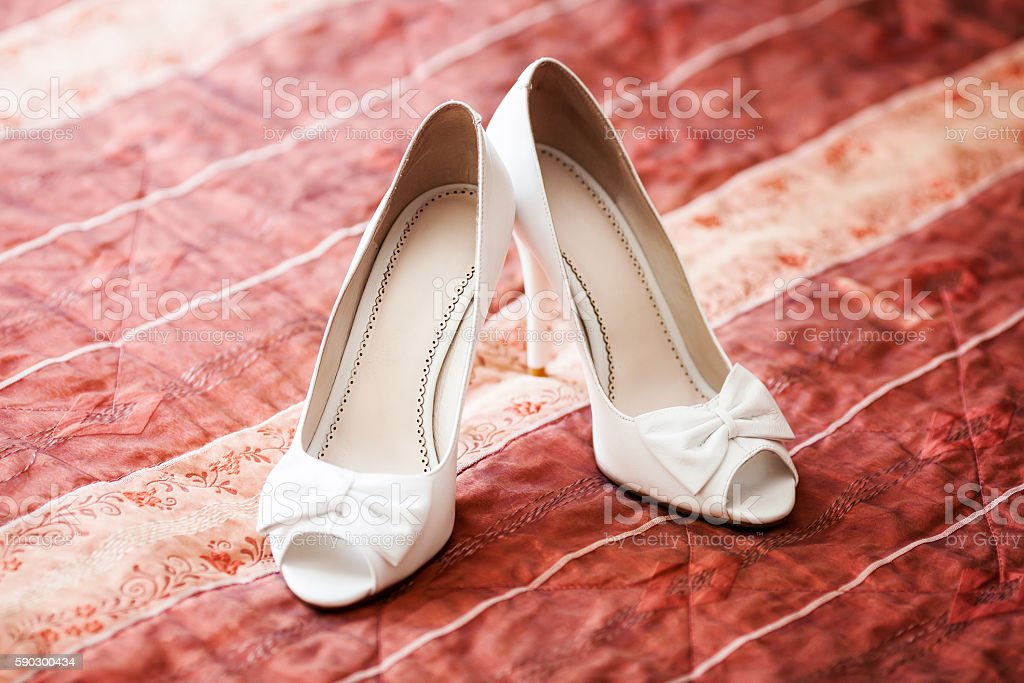 White bridal wedding shoes on red sofa. Marriage concept royaltyfri bildbanksbilder