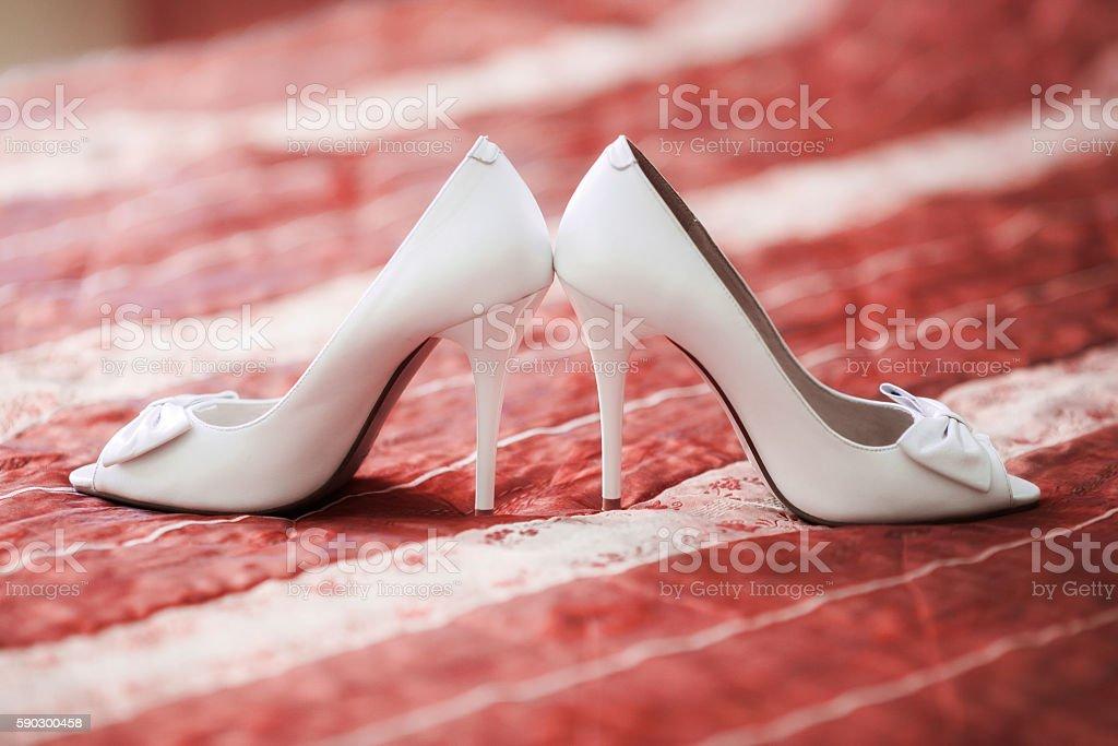 White bridal wedding shoes on red sofa. Marriage concept Стоковые фото Стоковая фотография
