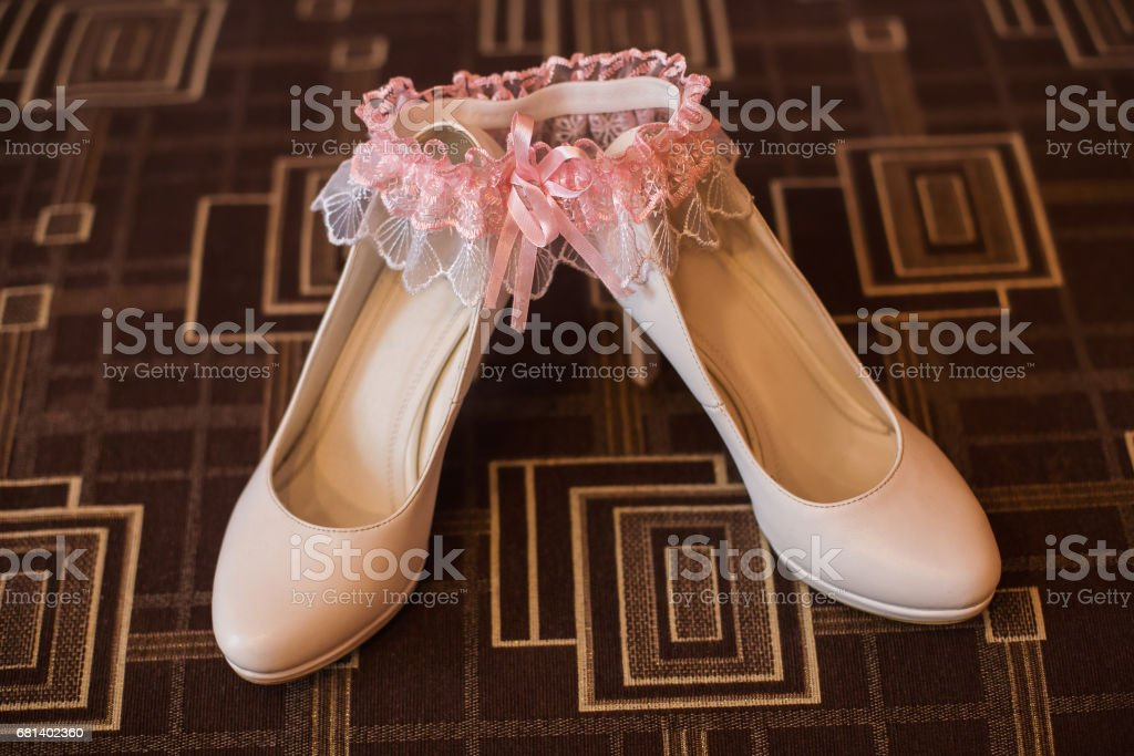 white bridal woman shoes, pink garter stock photo