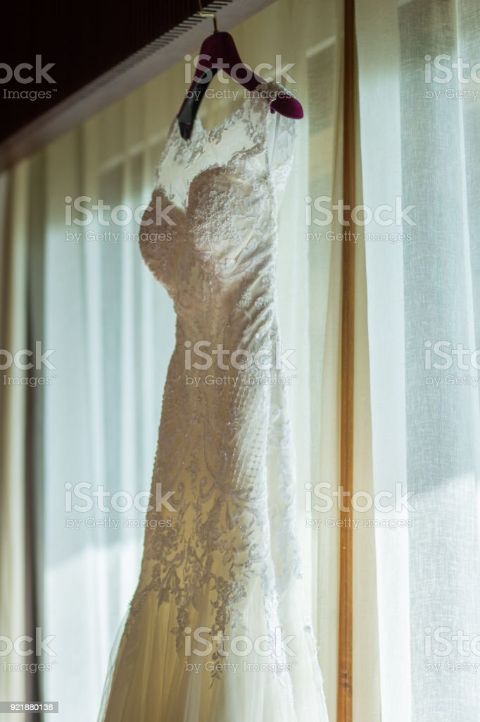 52bb0833f2e white bride dress hang against big door or window on white curtain with  sunlight royalty-