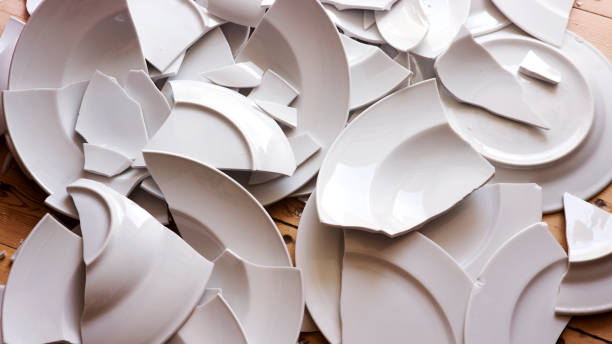 white broken plates on a wooden floor many white broken plates on a wooden floor demolishing stock pictures, royalty-free photos & images