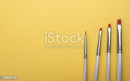 istock White Brushes set on yellow background 1076297154