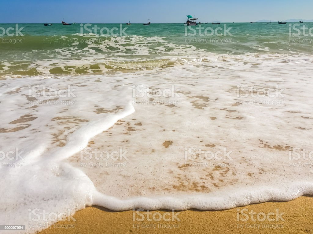 White bubbles created on the beach by ocean waves on seashore Foam bubbles abstract white background. Detergent white foam with some bubbles in it A wave thinning out of the sand of a beach stock photo