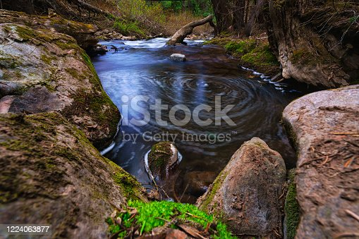 White Bubbles Rotating in Circle Along Scenic Mountain Creek - Nature landscape with stream of flowing water. Wilderness beauty.