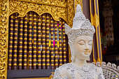 White Buddha statue with golden background at Chiang Mai, Thailand.