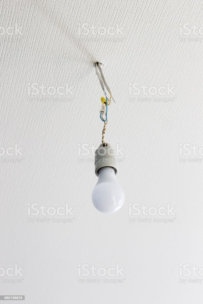 white bulb hanging from the white ceiling on wires royalty-free 스톡 사진