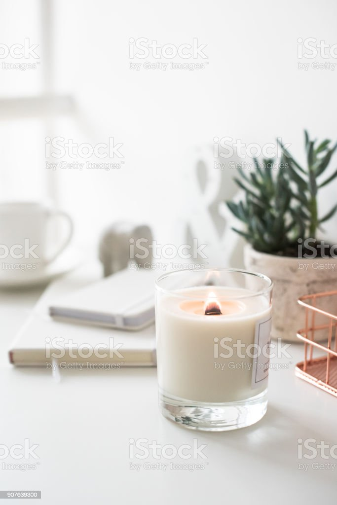 White burning candle on table, home interior decorations stock photo