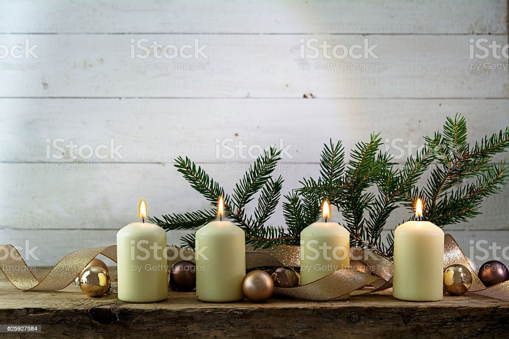 white burning candles on the fourth advent, rustic christmas decoration stock photo