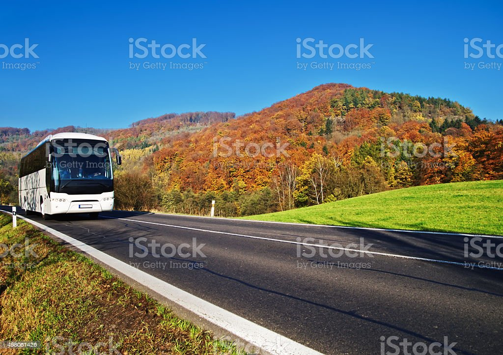 White Bus arriving at the asphalt road through the valley stock photo