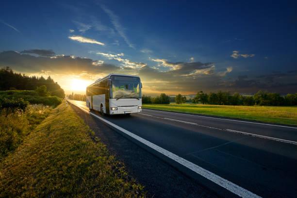 bus blanco que llega a la carretera de asfalto en un paisaje rural en los rayos de la puesta del sol - autobús fotografías e imágenes de stock