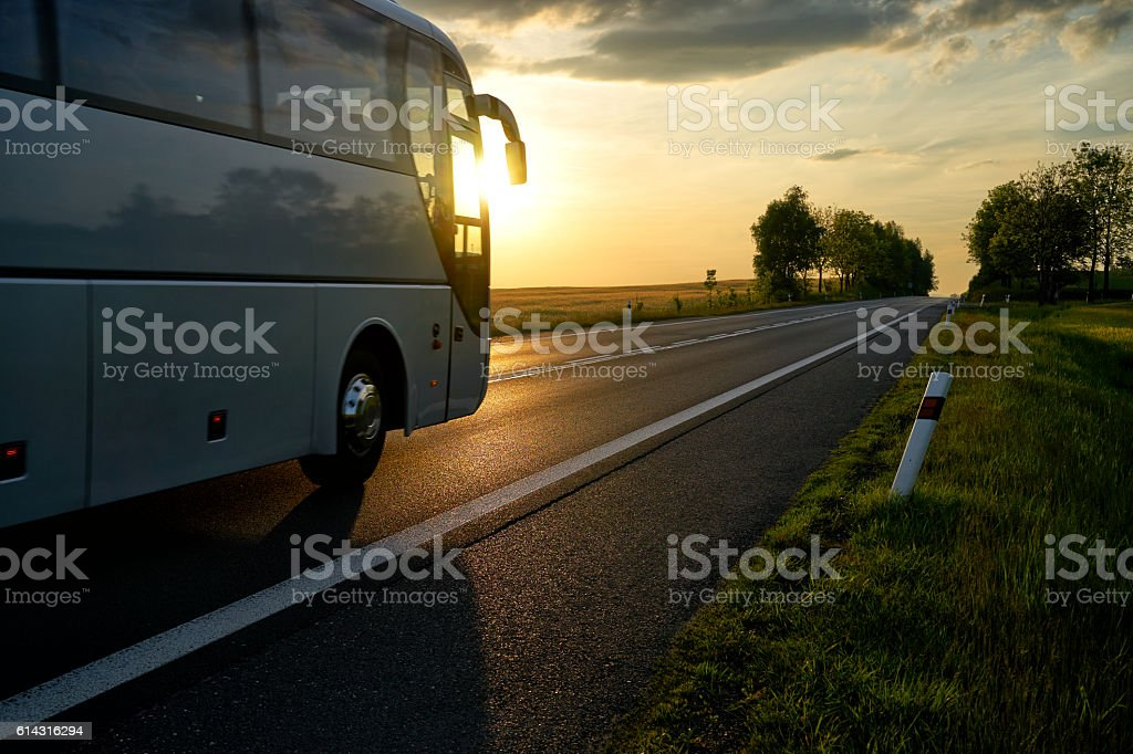 White Bus driving along the asphalt road at sunset. stock photo