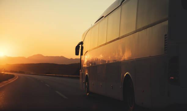 Autobús blanco conducir en el camino hacia la puesta de sol - foto de stock