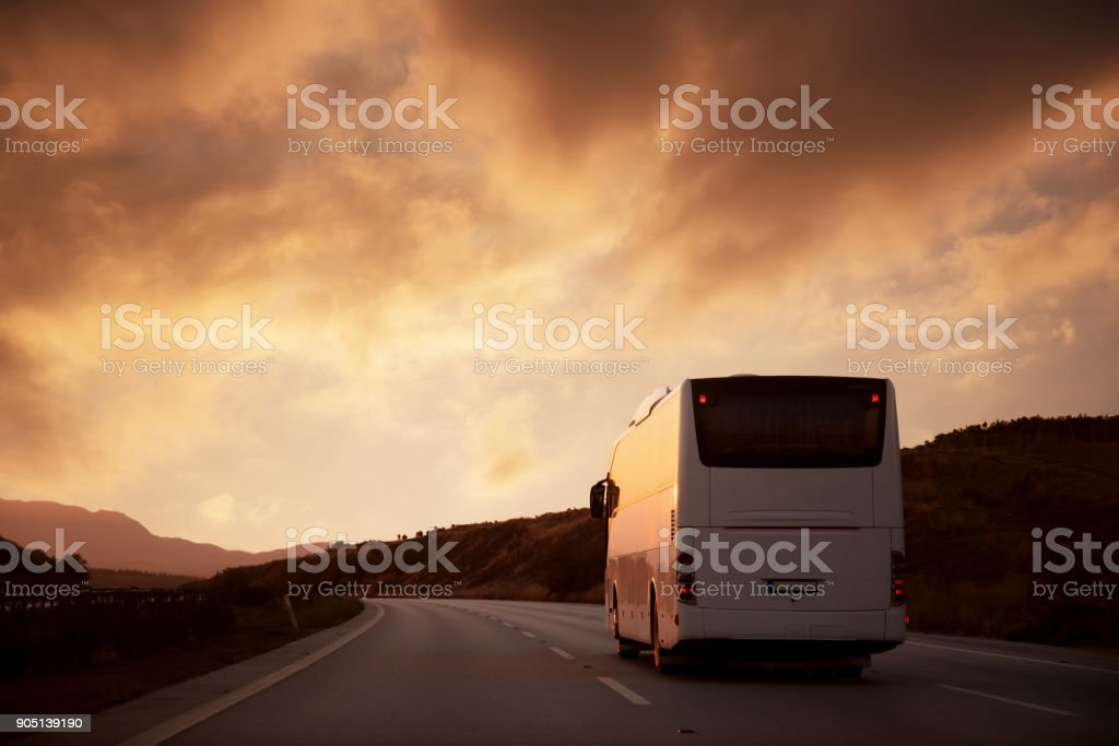 White bus driving on road towards the setting sun stock photo