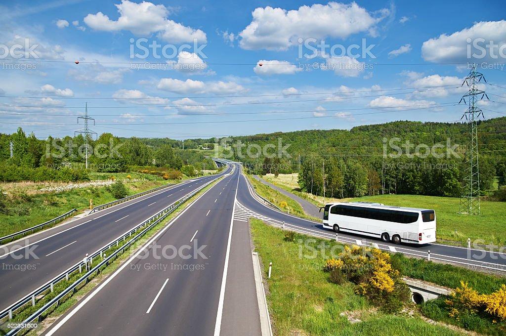 White Bus entering on an empty asphalt highway. stock photo