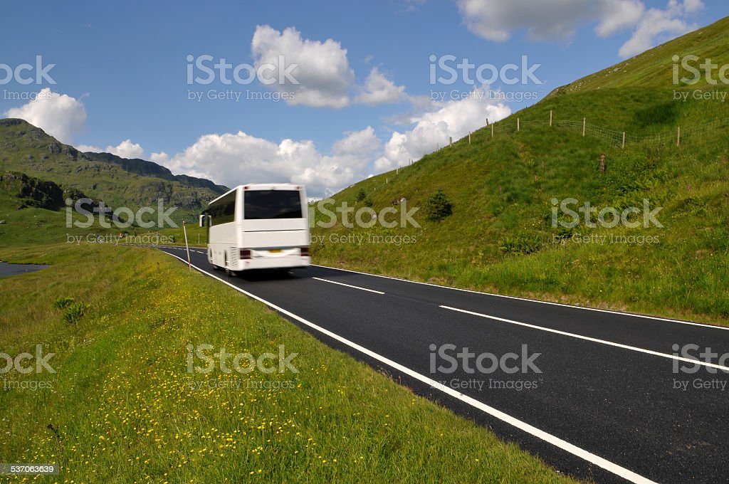 White bus on mountain road stock photo