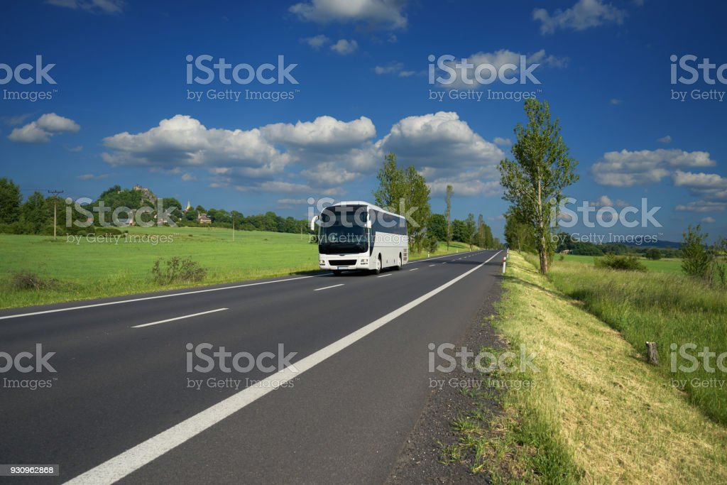 White bus traveling on asphalt road in a rural landscape. Village and mountain with castle ruins in the background. stock photo
